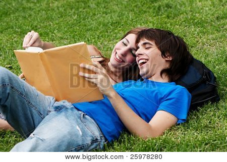 Couple students laying on the grass and reading a book