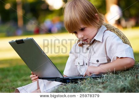 The boy reading notebook sitting in a haystack