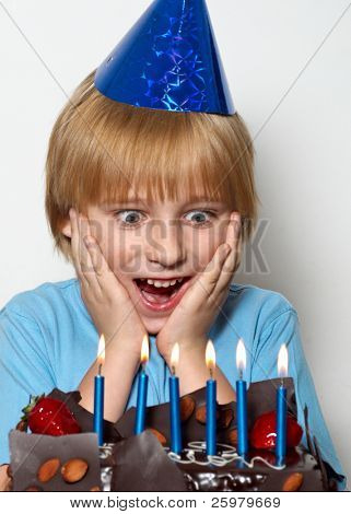 Portrait of little child with cap and cake at his birthday