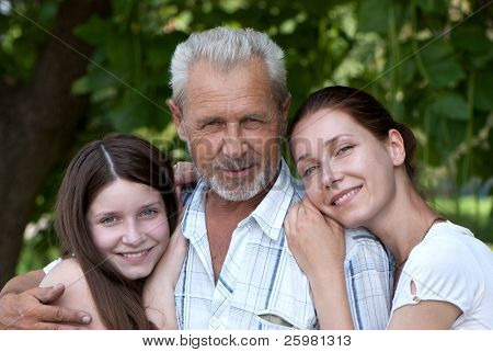 Portrait happy grandfather, daughte and granddaughter outdoor
