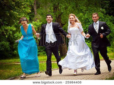 noivo e noiva feliz con frainds corre ao longo da viela no Parque