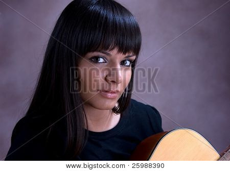 Portrait of beautiful young brunette playing guitar