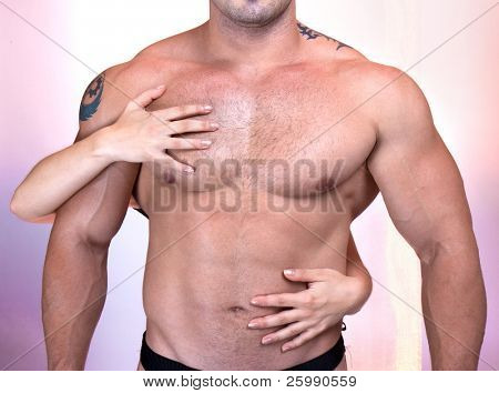 Woman's hands on a sexy man's torso