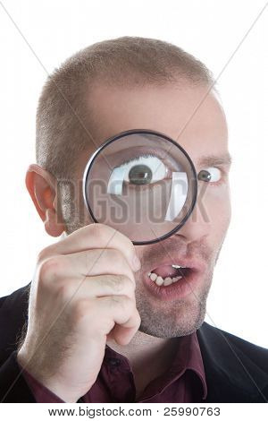 Businessman in a suit make a funny face through a magnifying glass