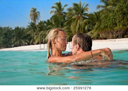 Retrato de pareja atractiva fan en la playa tropical