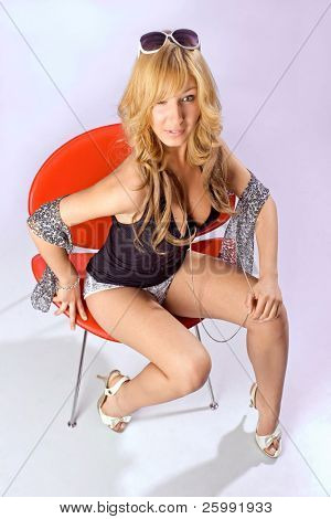Beautiful fashion woman portrait on red chair