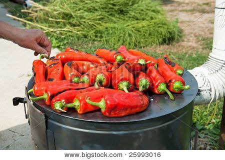 Roasting red paprika on range for winter provisions , autumn season