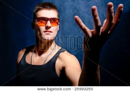 Suppliant looking male whit orange sunglasses hold hand up ,   dark background