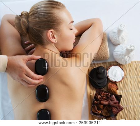 poster of Young woman getting hot stone massage in spa salon. Beauty treatment concept. The girl's relaxing on