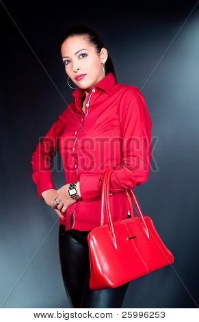 Beautiful brunette with red bag and shirt posing , studio shot