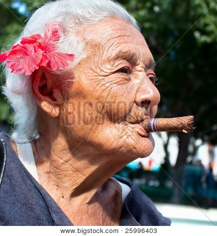 Old wrinkled woman with red flower smoking cigar. Santiago de Cuba, Cuba