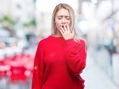 Young blonde woman wearing winter sweater over isolated background bored yawning tired covering mout poster