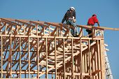 pic of 2x4  - unidentifiable construction workers work on framing a building - JPG