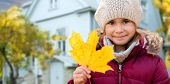 childhood, season and real estate concept - close up of happy little girl with fallen maple leaf in  poster