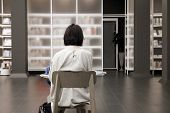 Young Female Student Study In Library. She Reading A Book On Table Doing Assignments In College Libr poster