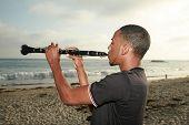 Постер, плакат: молодой человек играет его Кларнет вне на пляже для всех чтобы слышать и наслаждаться