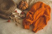 Cozy Knitted Warm Orange Sweater With Old Books And Vintage Straw Bag On White Warm Plaid With Pumpk poster