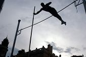 stock photo of pole-vault  - Silhouetted athlete clearing the bar during a pole vault event - JPG