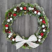Christmas wreath with winter flora of holly, mistletoe, ivy, snow covered spruce fir and pine cones  poster