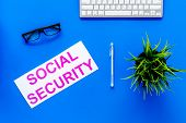 Social Security Concept. Printed Words Social Security On Blue Office Desk Background With Computer  poster