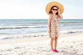 Little girl on the beach wearing yellow funny hat.