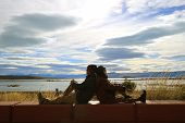 Couple Enjoy The Warm Sunlight Together By The Lake Shore Of Lake Argentino In El Calafate, Patagoni poster