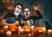 Father and his kid having fun at home. Happy family celebrating Halloween. People wearing carnival c poster