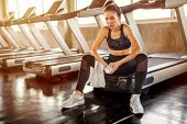 Beautiful Asian Young Woman Tired Taking A Break From Running Or Exercise Sitting On Treadmill Machi poster