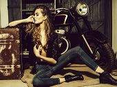 Girl Biker Or Pretty Woman With Long, Blond Hair In Erotic Shirt And Jeans With Vintage Suitcase At  poster