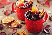 Two Cups Of Autumn Mulled Wine Or Gluhwein With Spices And Orange Slices On Rustic Table Top View. T poster