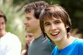 Portrait young happy teenage boy at the park with friends