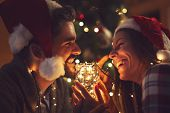 Young Couple In Love Sitting By The Fireplace And Nicely Decorated Christmas Tree, Enjoying The Chri poster