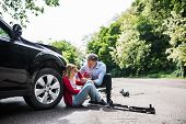 Young Woman By The Car After An Accident And A Man Helping Her. poster