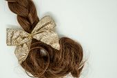 Beautiful Braided Brown Hair Isolated On White, Glittery Gold Bow Attached At The End Of The Braid. poster