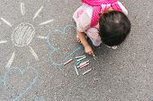 Top View Image Of Happy Little Girl Wears Pink Dress And Backpack Drawing With Colorful Chalks On Th poster