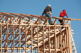 stock photo of 2x4  - unidentifiable construction workers work on framing a building - JPG