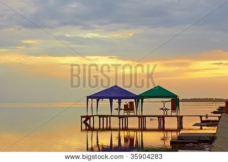 Tents Above Sea Water At Sunset