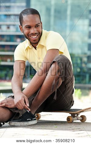 Young Male Sitting On Skateboard