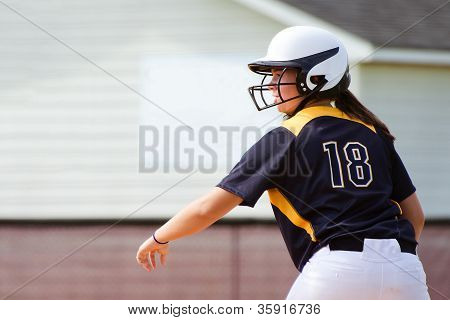 Teen girl playing softball in organized game