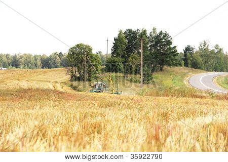 Tractor With Hay At Field In Summer Day