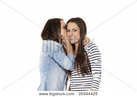 young teenager whispering chit-chat to her laughing friend