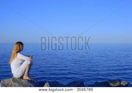 Girl Sitting On The Rock By The Peaceful Sea