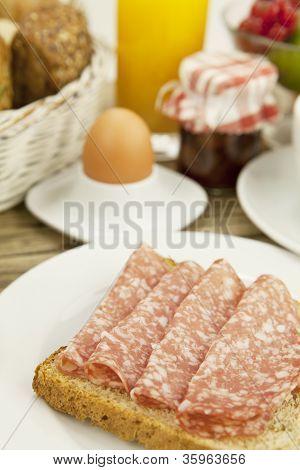 Tasty Breakfast With Salami Toast On Table