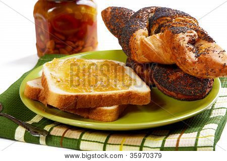 Pieces Of Bread With Jam And Rolls On A Kitchen Table