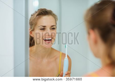 Happy Young Woman Using Electric Toothbrush In Bathroom