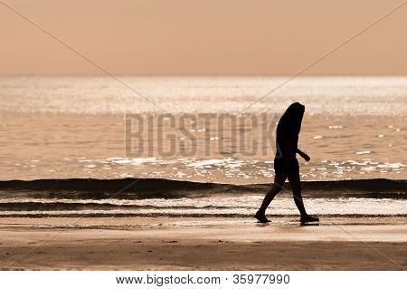 Sillhouette Woman Walking On The Beach