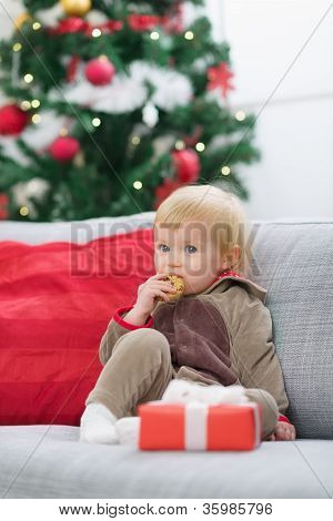 Baby In Suit Of Santa's Little Helper With Christmas Gift Eating
