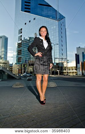 Pretty Woman Posing In Front Of Modern Office Building