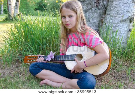 girl with guitar by tree