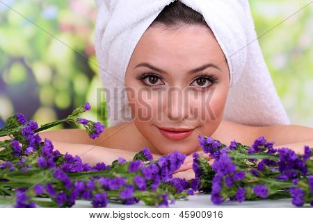 Beautiful young woman with towel on her head and flowers on bright background